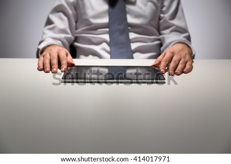 Businessman using tablet on empty table. Mock up