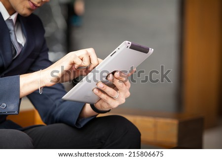 Businessman using tablet PC at the hotel lobby.  - stock photo