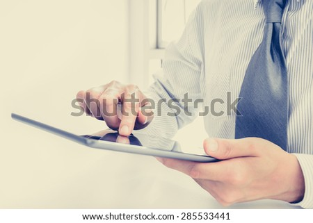 Businessman using tablet pc with one hand touching the screen - vintage tone