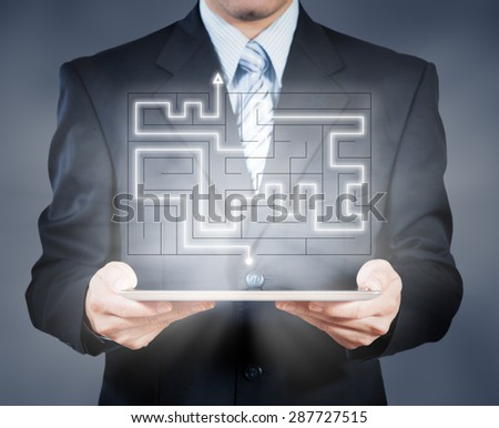 Businessman using tablet showing maze, business decision concept - stock photo