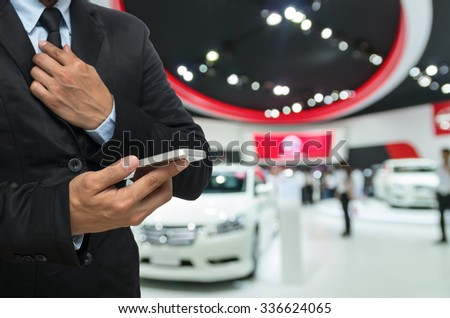 Businessman using the Smart mobile phone on abstract blurred photo of motor show background