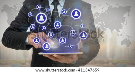 Businessman using the tablet for social connection with cityscape and financial graph on blurred building background, Elements of this image furnished by NASA, Business network concept