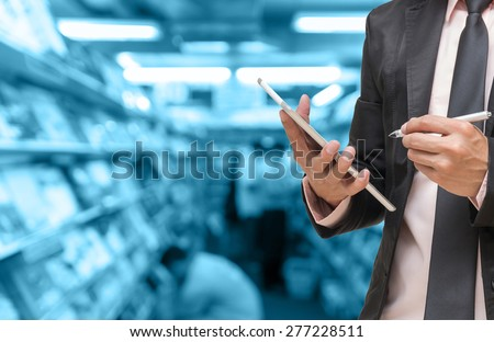 Businessman using the tablet on on Abstract blurred photo of book store with people background,blue color tone - stock photo
