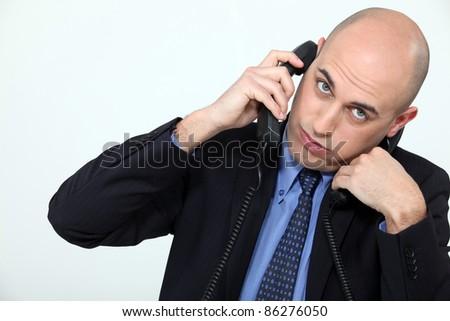 Businessman using two phones - stock photo