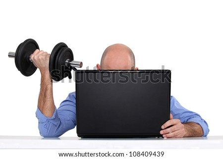 Businessman using weights at his desk - stock photo