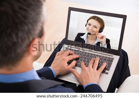 Businessman Video Chatting With Businesswoman On Laptop - stock photo