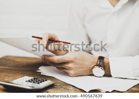Businessman viewing financial statements. Focus on hand and pen.