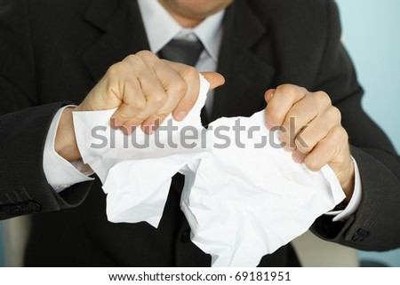 Businessman violently tormented the paper in his hands - stock photo