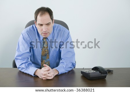 Businessman waiting for a phone to ring - stock photo