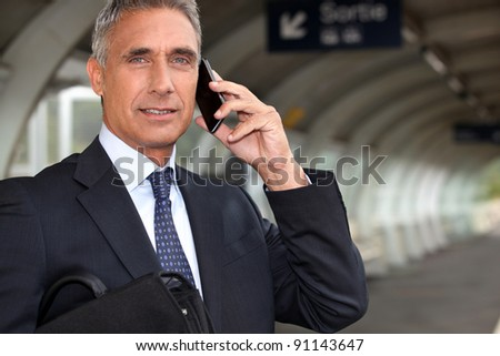 Businessman waiting for a train on the platform - stock photo