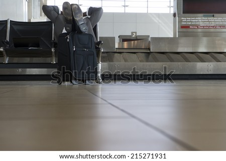 Businessman waiting for luggage in airport baggage claim area, feet up, hands behind head, low section - stock photo