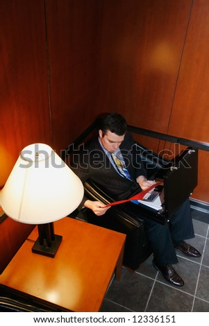 Businessman waiting in an office lobby with his briefcase open - stock photo