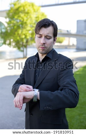 businessman waiting outside and looking at his watch - stock photo