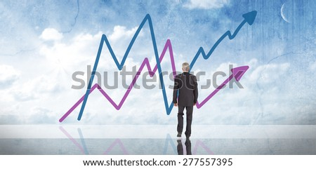 Businessman walking against painted blue sky