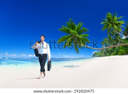 Businessman walking along the tropical beach. - stock photo