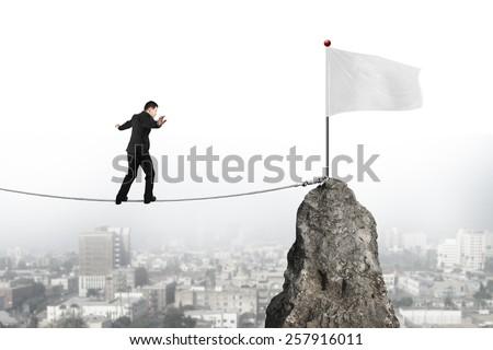 Businessman walking and balancing on rope toward white flag of mountain peak with cityscape background - stock photo
