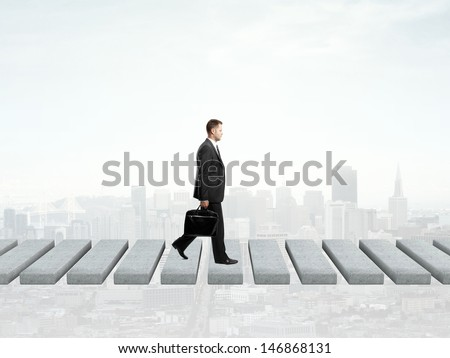 businessman walking and city on background - stock photo