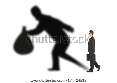 businessman walking and holding bag  with thief shadow - stock photo
