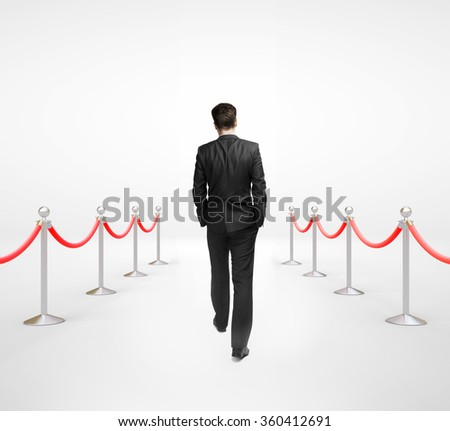 businessman walking and stanchions barrier in white room - stock photo