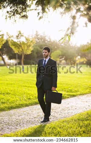 Businessman walking at the city garden - stock photo