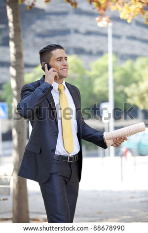 Businessman walking at the city park and  calling at the cellular with a newspaper