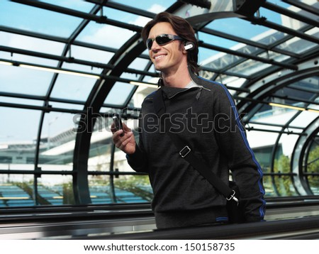 businessman walking down the airport and talking by mobile phone - stock photo