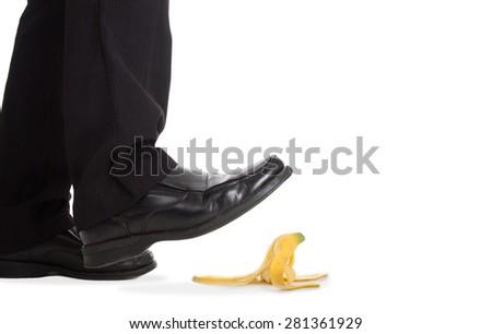 Businessman walking foot press banana peel and slip fall to floor. - stock photo