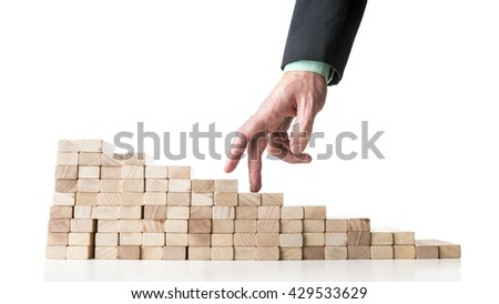 Businessman walking his fingers up wooden pegs resembling a staircase, isolated over white background.