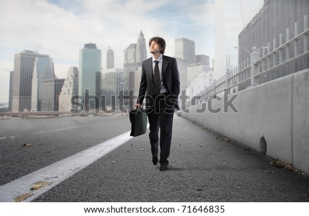 Businessman walking on a city street - stock photo