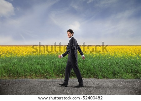 Businessman walking on a countryside road