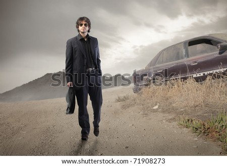 Businessman walking on a countryside road - stock photo