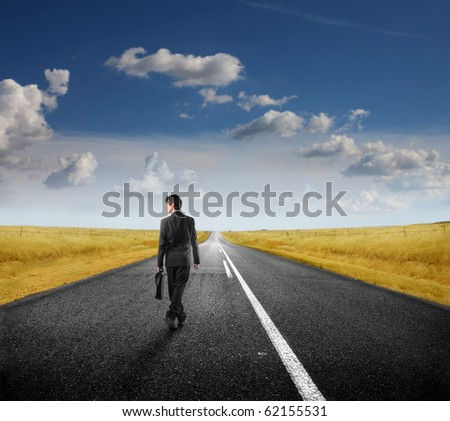 Businessman walking on a road - stock photo