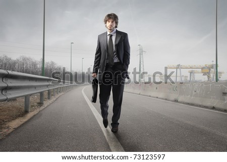 Businessman walking on a road