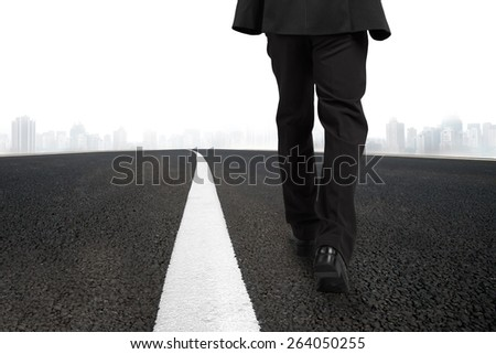 Businessman walking on asphalt road with white line and urban scene - stock photo