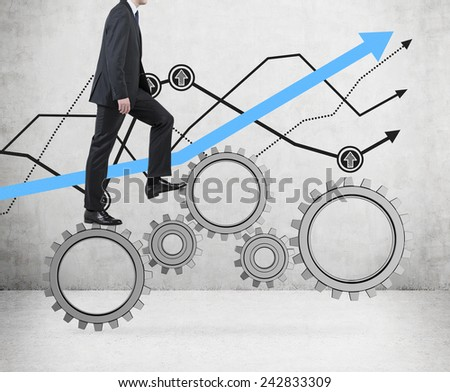 businessman walking on cogs and drawing graph on wall - stock photo