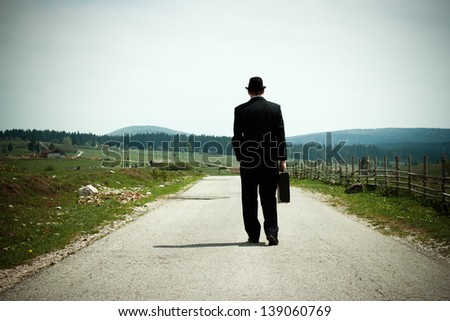 Businessman walking on country road and thinking,Time for contemplation