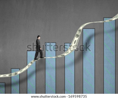 Businessman walking on growth money trend with chart in concrete wall background - stock photo
