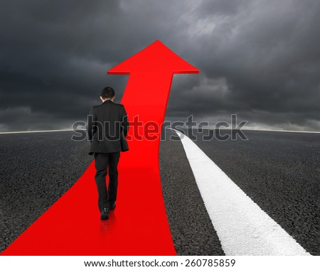 Businessman walking on red arrow up road with asphalt pavement and overcast background - stock photo