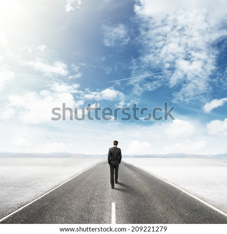 businessman walking on road in desert - stock photo