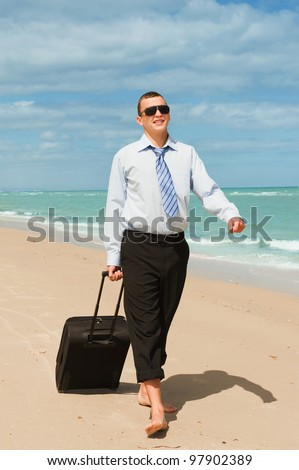 Businessman walking on the beach the first day of vacation