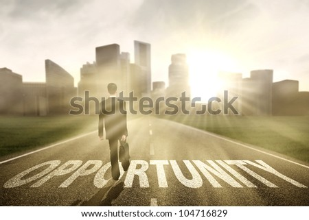 Businessman walking on the highway road to new city, symbolizing as the way to the new opportunity - stock photo