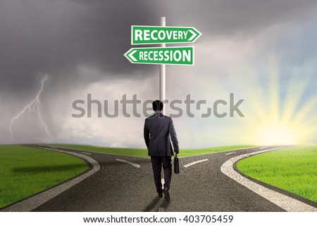 Businessman walking on the road with two words of recession and recovery on the signpost pointing the way - stock photo