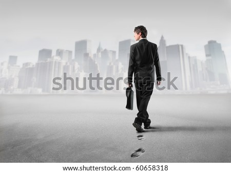 Businessman walking on the sand with cityscape on the background - stock photo