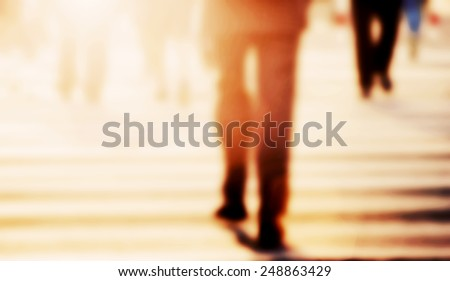 Businessman walking on the street. Blur, vintage mood. Pedestrians in the background - stock photo