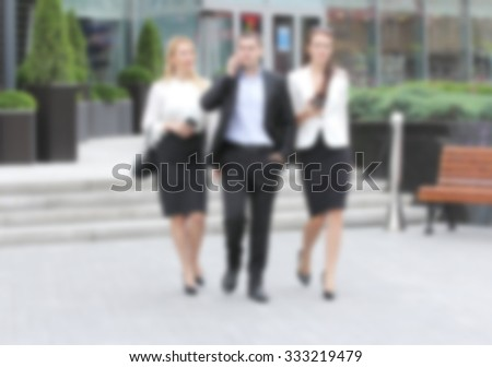 Businessman walking on the street with their secretaries, in front of office. Creative abstract blur background with bokeh effect
