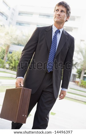 Businessman walking outdoors - stock photo