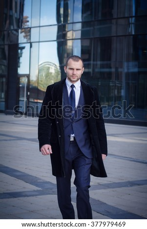 businessman walking outdoors in front of a modern office building - stock photo