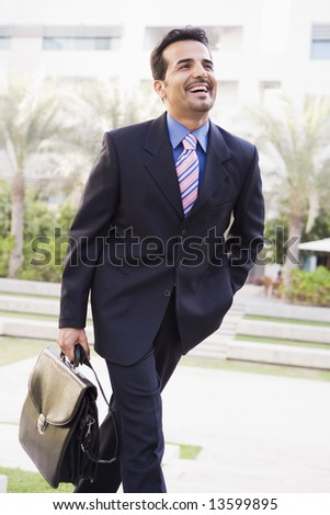 Businessman walking to office carrying briefcase - stock photo