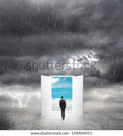 businessman walking to opened door from bad weather to good - stock photo