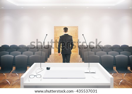 Businessman walking towards exit door in conference hall interior with speaker's stand, rows of seats, wooden floor, concrete walls and ceiling. 3D Rendering - stock photo